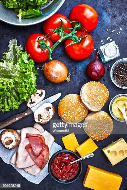 Ingredients of burgers on dark ground, elevated view