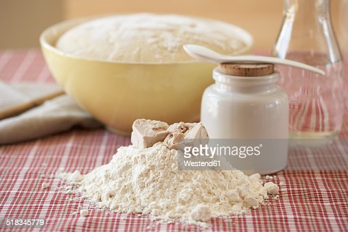 Ingredients of yeast dough and bowl of raw yeast dough on cloth