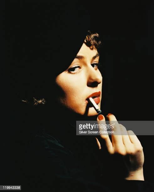 Ingrid Bergman Swedish actress smoking a cigarette against a black background circa 1940