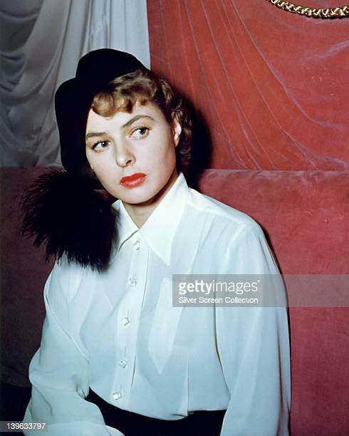 Ingrid Bergman Swedish actress wearing a black hat and a white blouse in a studio portrait against a red background circa 1945