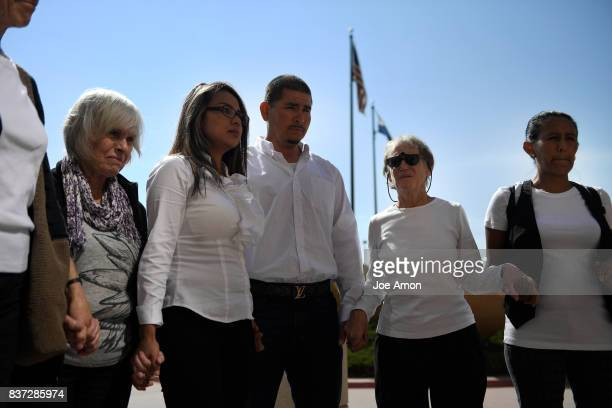 Ingrid Encalada Latorre and her partner Eliseo Jurado pray with Metro Denver Sanctuary Coalition members after her hearing at the Jefferson County...