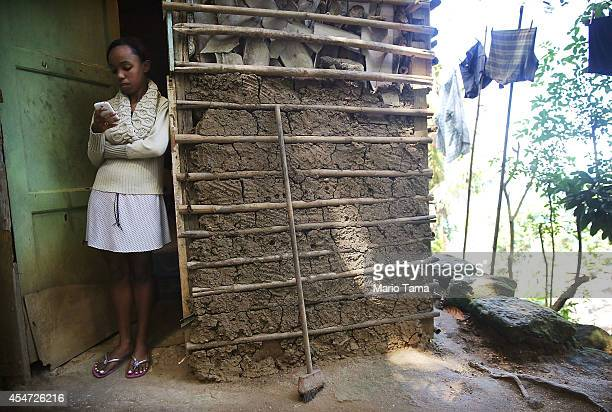 Ingrid Santos checks her mobile phone in the doorway of her home constructed from mud and wood in the Babilonia favela or community on September 5...