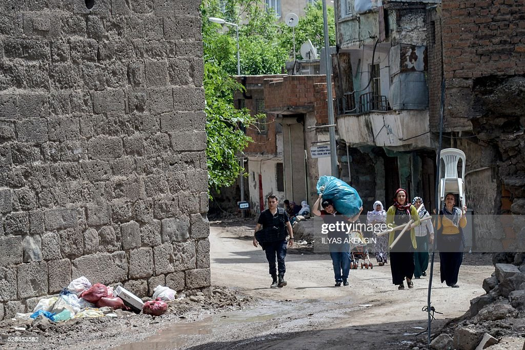 Inhabitants carry belongings from their homes in the historical district in Diyarbakir, southeastern Turkey, on May 5, 2016. / AFP / ILYAS