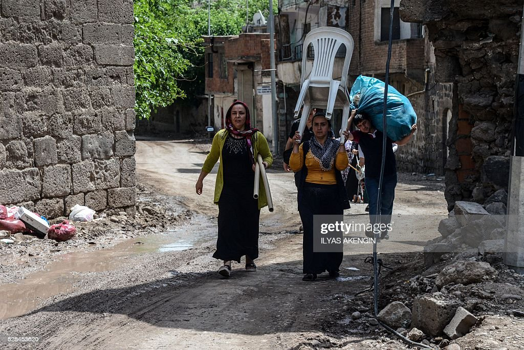 Inhabitants carry their belongings from their homes in the historical district in Diyarbakir, southeastern Turkey, on May 5, 2016. / AFP / ILYAS