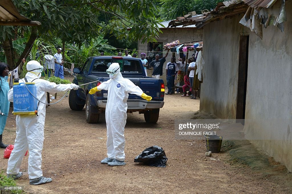 Inhabitants look at medical workers of the Liberian Red Cross disinfecting themselves after an intervention in the small city of Banjol where three...