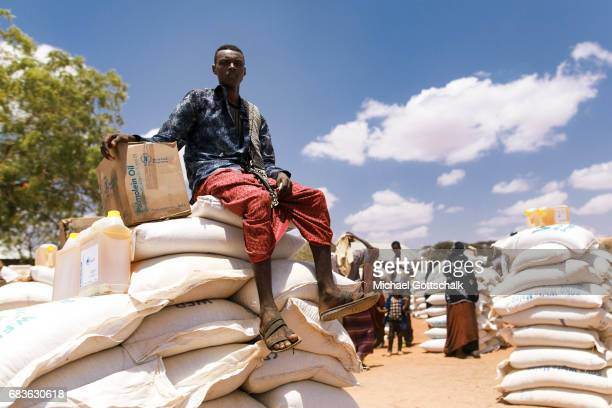Inhabitants of a village in the Somali region in Ethiopia where Pastorale settled because of the persistent drought A young man is sitting on food...