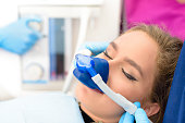Beautiful getting woman inhalation sedation at dental clinic