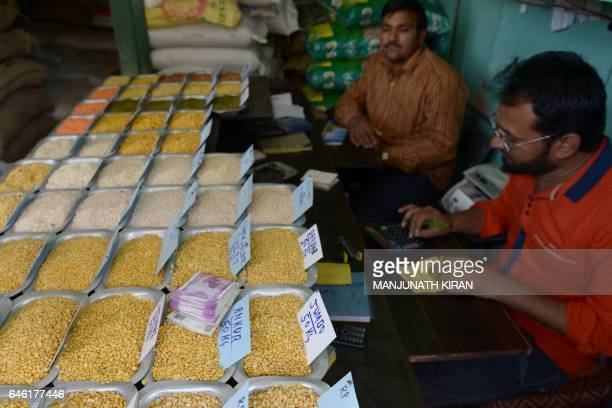 Inidan currency of various denominations placed by a customer lies on the table displaying food grains while a merchant makes calculations at a...