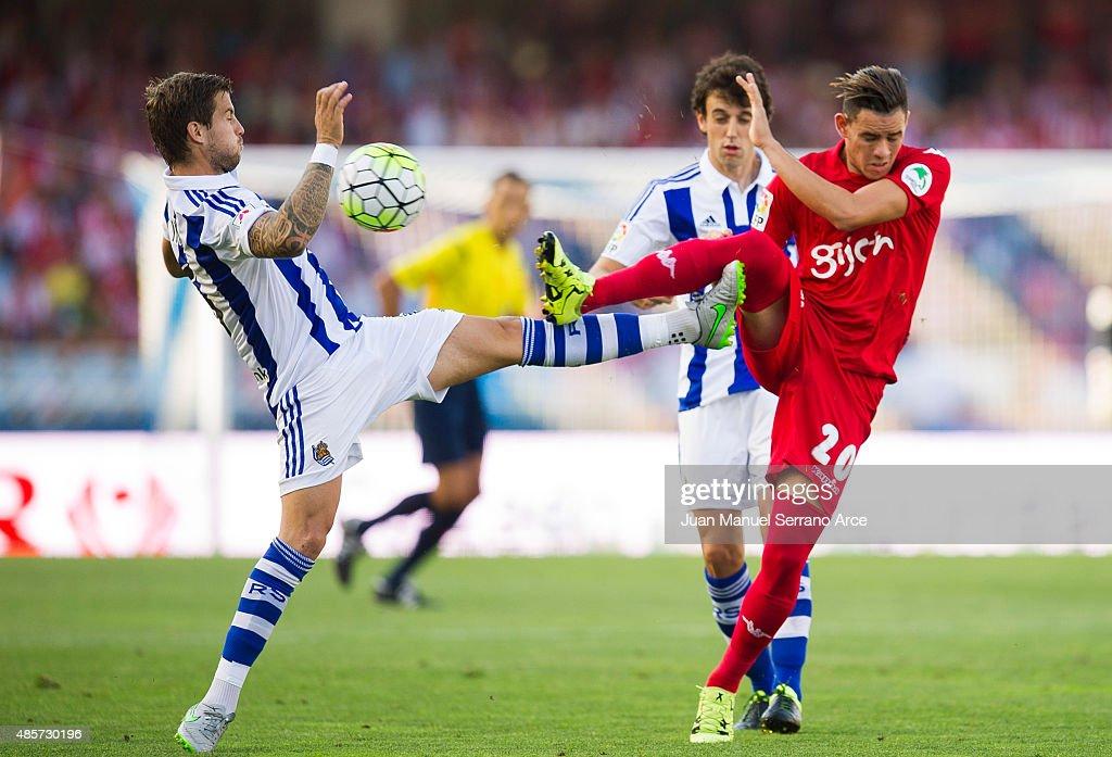Inigo Martinez of Real Sociedad de Futbol duel for the ball with Arnaldo Sanabria of Sporting Gijon during the La Liga match between Real Sociedad de...