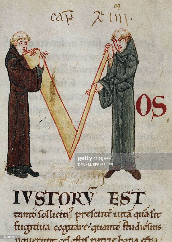 Initial capital letter F depicting two monks folding a length if linen miniature from the Morals on the Book of Job by Saint Gregory the Great...