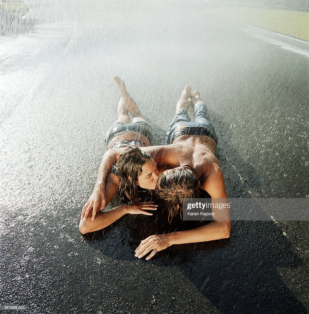 Initimate young couple lying on road in rain : Stock Photo