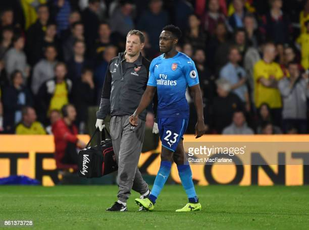 Injured Arsenal striker Danny Welbeck leave the pitch with physio Colin Lewin during the Premier League match between Watford and Arsenal at Vicarage...