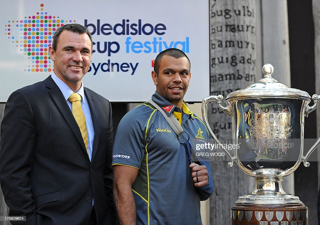 Injured Australian Wallabies rugby union fullback Kurtley Beale (C) and retired Australian player Joe Roff (L) pose with the Bledisloe Cup during the official Bledisloe Cup Festival launch in Sydney on August 9, 2013. New Wallabies' coach Ewen McKenzie named eight uncapped players in his inaugural 30-man Wallabies' squad on August 9 for this month's Rugby Championship, with the opening Test against New Zealand in Sydney on August 17. AFP PHOTO / Greg WOOD