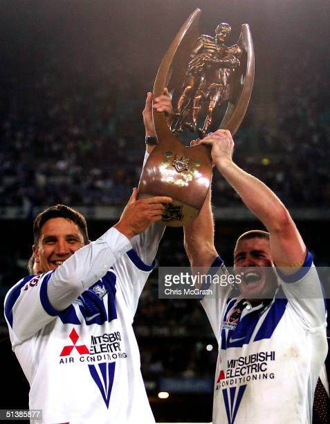 Injured Bulldogs captain Steve Price and stand in captain Andrew Ryan hold aloft the NRL trophy during the NRL Grand Final between the Sydney...