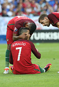 Injured Cristiano Ronaldo of Portugal is consoled by Luis Nani during the UEFA Euro 2016 final match between Portugal and France at Stade de France...