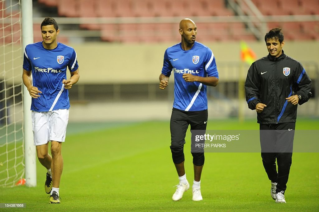 Injured French footballer Nicolas Anelka (C) and Colombian midfielder Giovanni Moreno (L) run with their fitness coach Santana Martel Luciano (R) as their Shanghai Shenhua team mates warm up before a training session at Hongkou stadium in Shanghai on October 19, 2012. Football star Didier Drogba is also injured so he will not play the next match for his Chinese club after returning from international duty and into a row that has seen his teammates reportedly refusing to practise over unpaid wages. AFP PHOTO/Peter PARKS
