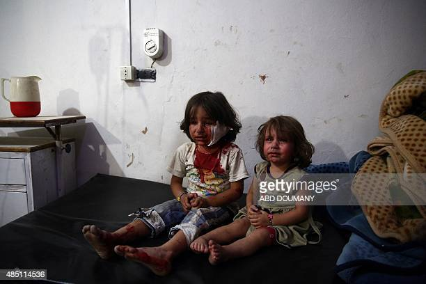 Injured girls await treatment at a make shift hospital in the rebelheld area of Douma east of the capital Damascus following reported air raids by...