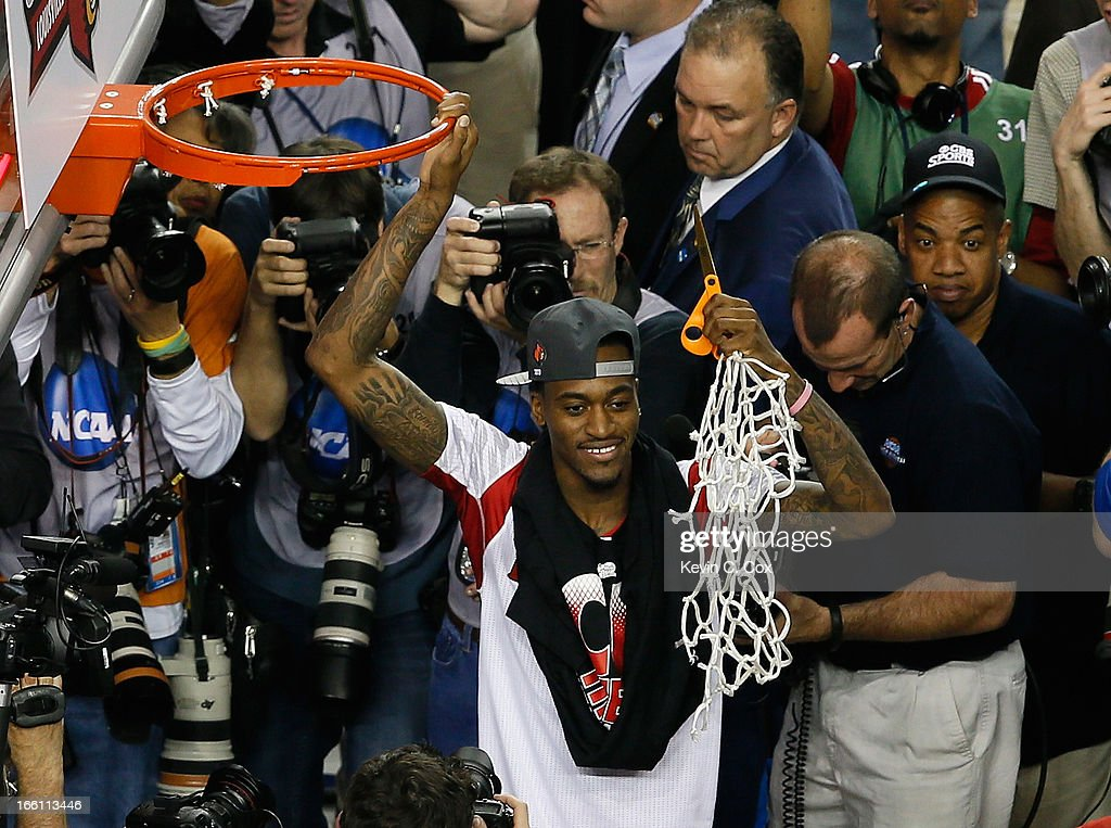 Injured guard Kevin Ware of the Louisville Cardinals celebrates after he cut down the net after Louisville won 8276 against the Michigan Wolverines...