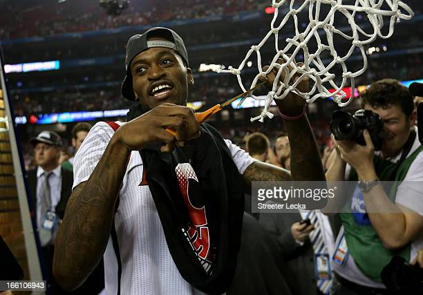 Injured guard Kevin Ware of the Louisville Cardinals celebrates as he cuts down the net after Louisville won 8276 against the Michigan Wolverines...