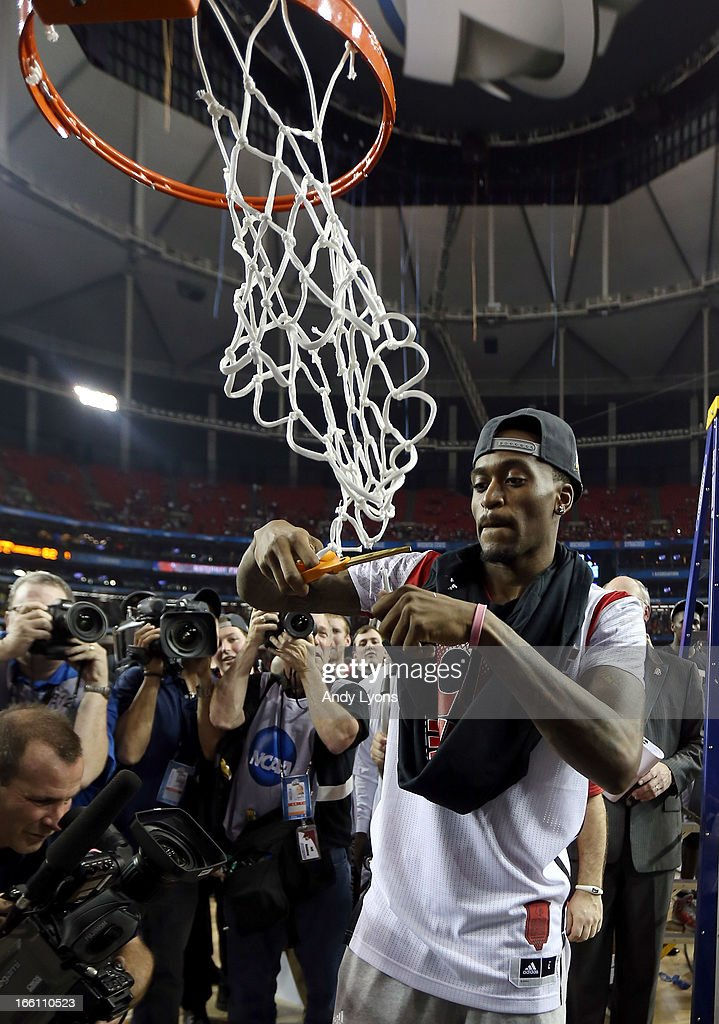 Injured guard Kevin Ware of the Louisville Cardinals celebrates by cutting down the net after they won 8276 against the Michigan Wolverines during...