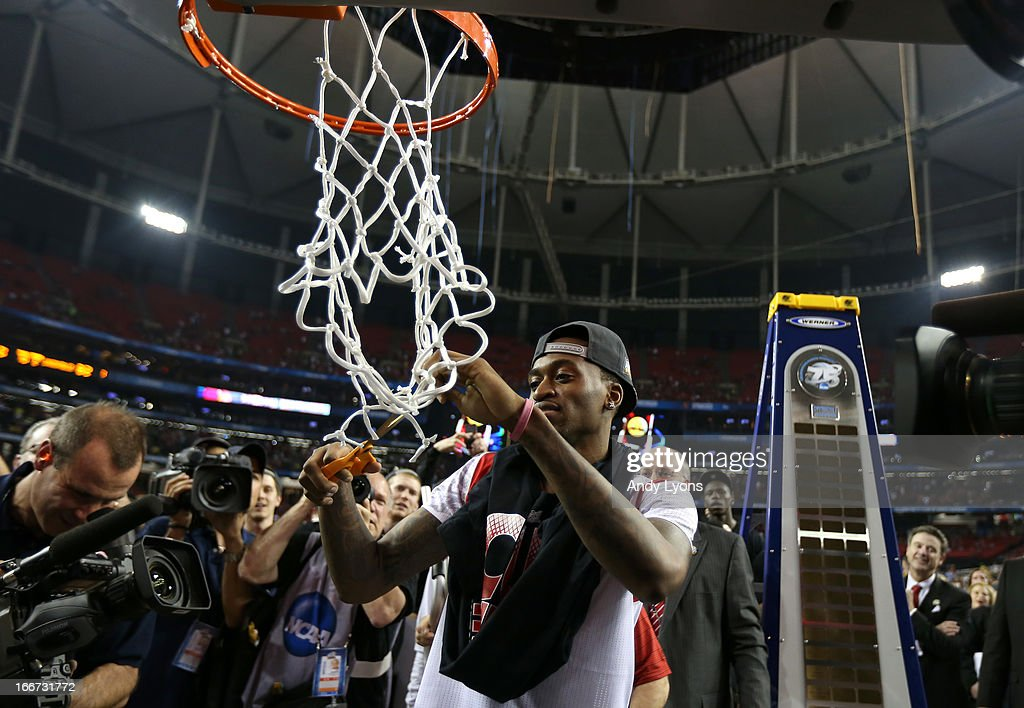 Injured guard Kevin Ware of the Louisville Cardinals cuts down the net in celebration of Louisville defeating the Michigan Wolverines during the 2013...
