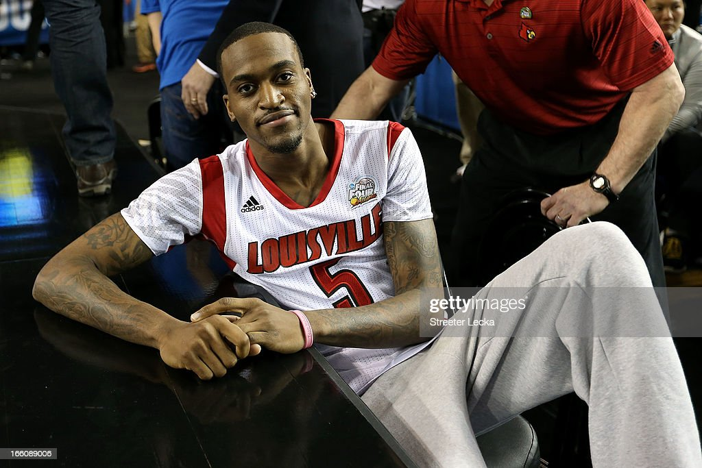 Injured guard Kevin Ware of the Louisville Cardinals leans on the court as the Cardinals get set to play against the Michigan Wolverines during the...