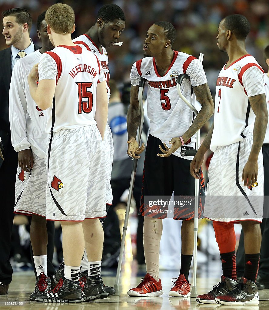 Injured guard Kevin Ware of the Louisville Cardinals talks with teammates Tim Henderson Montrezl Harrell and Russ Smith during a timeout in the...