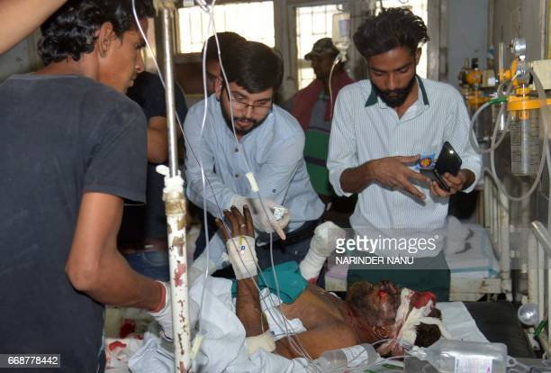 Injured Indian patient Tarsem is treated by medical staff as he lies in a ward at the Guru Nanak Dev Hospital in Amritsar on April 15 after an...