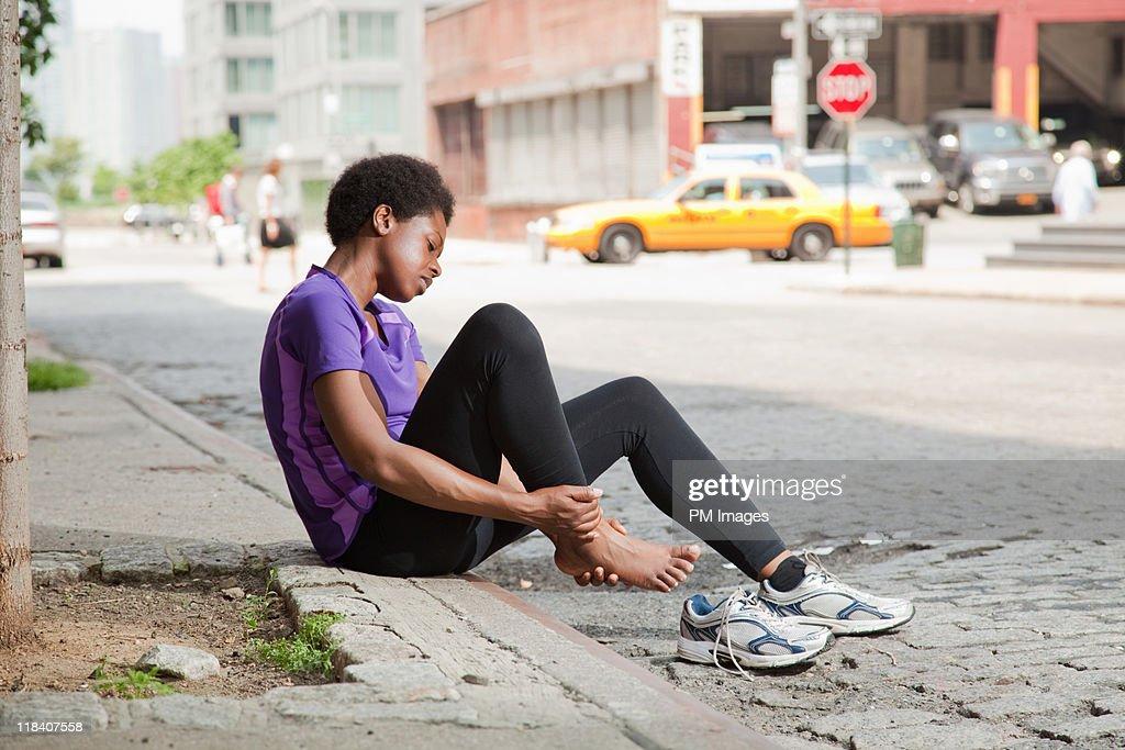 Injured jogger on city street : Stock Photo