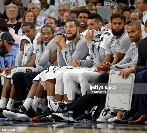 Injured Kawhi Leonard of the San Antonio Spurssecond from end on the left enjoys the action during game against the Denver Nuggetsat ATT Center on...