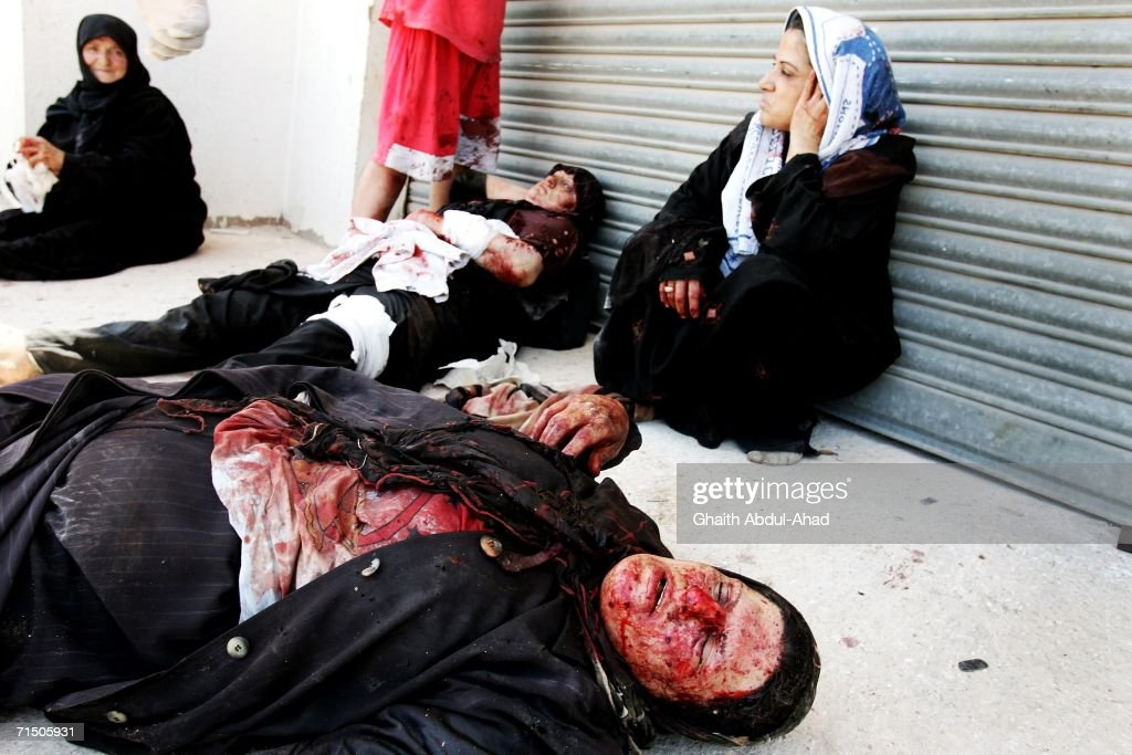 Injured Lebanese people are seen on the ground after a rocket from an Israeli aircraft hit their van as they fled their village July 23, 2006 in Tyre, Lebanon. According to reports, at least 130 people have died in Tyre since the begining of the airstrikes.