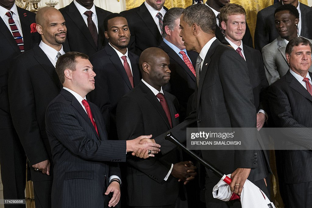 Injured Louisville Cardinals basketball player Kevin Ware watches as US President Barack Obama greets his teammates during an event in the East Room...