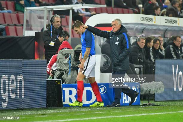 Injured Lucas Digne of France is substitited by France coach Didier Deschamps during the international friendly match between Germany and France at...
