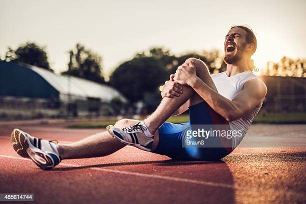 Injured male athlete screaming in pain at sunset.