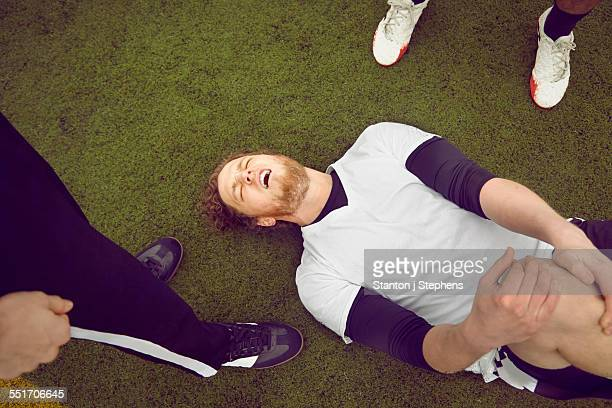 Injured male soccer player on soccer pitch