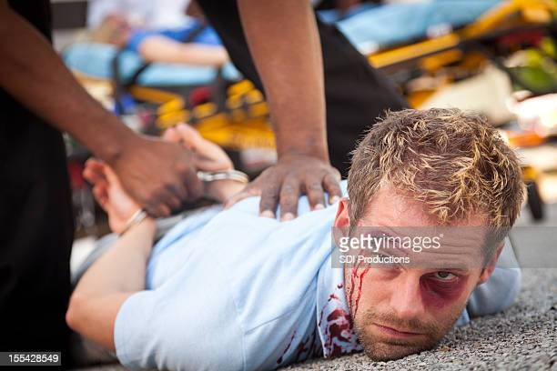 Injured man being forced down and arrested