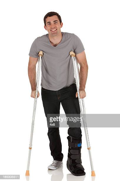 Injured man walkiing with the help of crutches