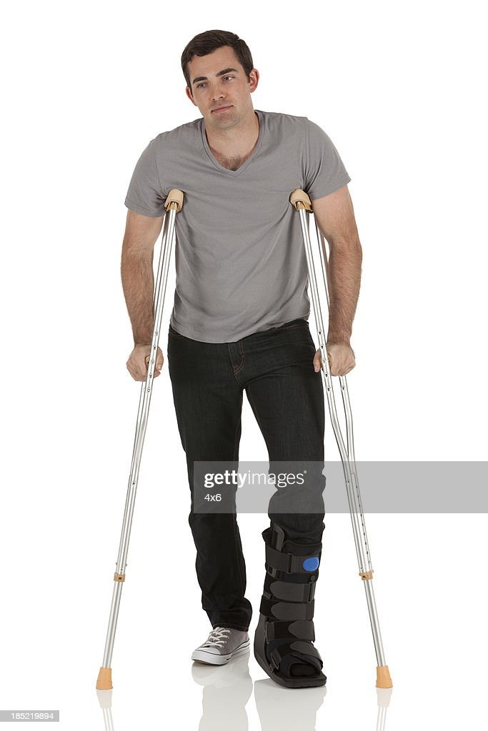 Injured man walking with the help of crutches