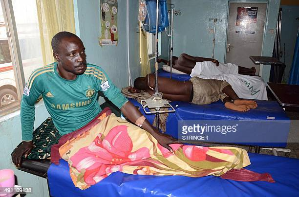 Injured men rest on hospital beds in Kuje near Abuja on October 3 after two explosions ripped through the outskirts of Nigeria's capital Abuja and...