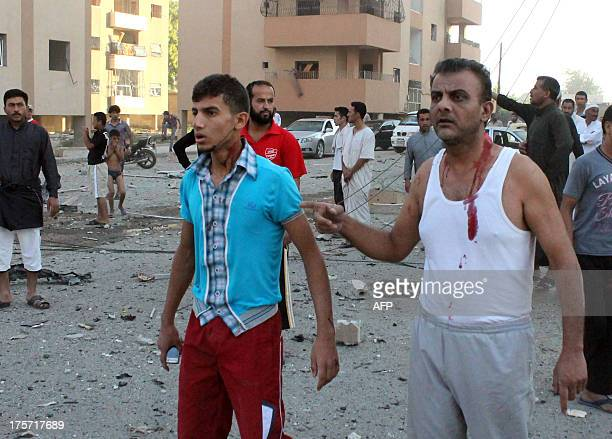 Injured men walk away from the scene of an explosion in the northern Syrian city of Raqqa early on August 7 2013 UN weapons inspectors tasked with...