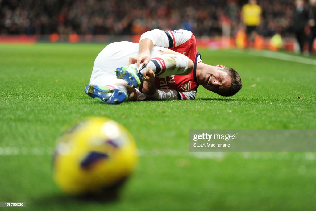 Injured Olivier Giroud of Arsenal lies on the pitch during the Barclays Premier League match between Arsenal and Newcastle United at Emirates Stadium on December 29, 2012 in London, England.