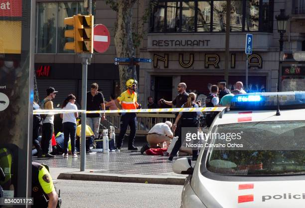 Injured people are tended to as police investigate near the scene of a terrorist attack in the Las Ramblas area on August 17 2017 in Barcelona Spain...