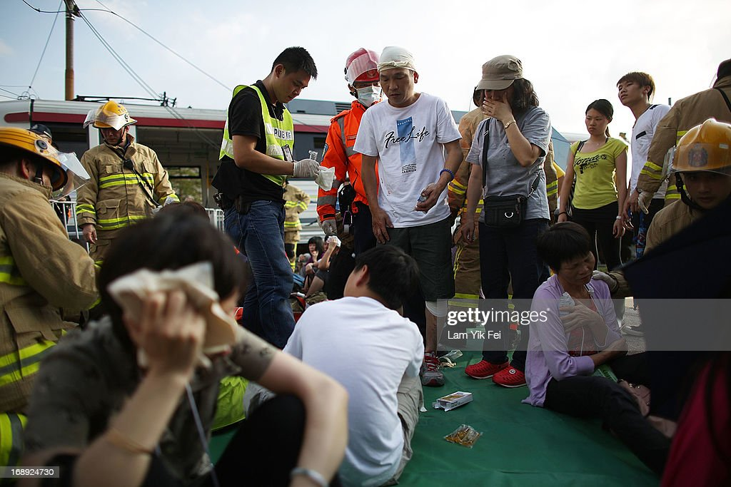 Injured people gather beside the derailed trains after the crash of two light railway trains on 17 May, 2013, near Hang Mei Tsuen Station at Tin Shui Wai in Hong Kong. Over 62 people are hurt in the accident, in which three victims are seriously injured. on May 17, 2013 in Hong Kong, Hong Kong.
