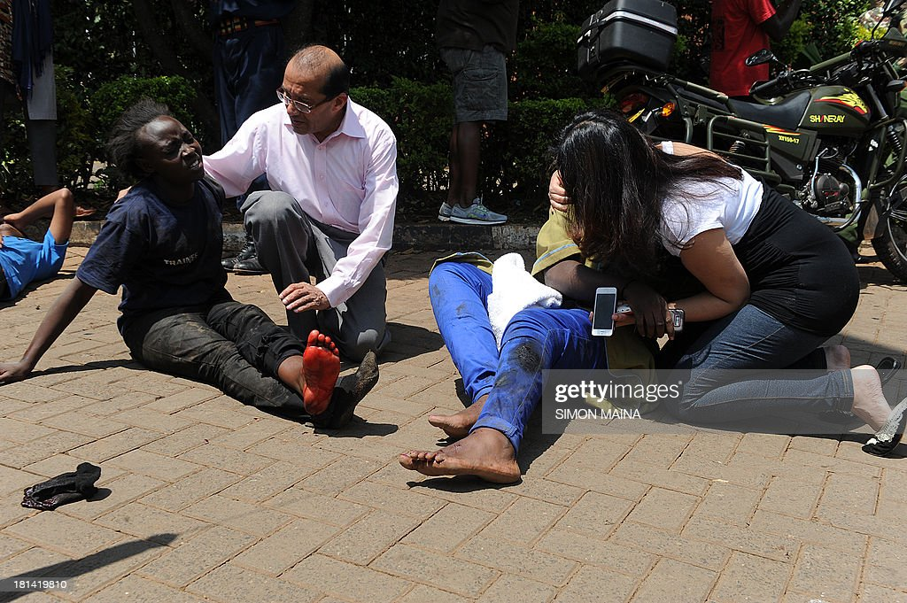 Injured people receive assistance from bypassers after masked gunmen stormed an upmarket mall and sprayed gunfire on shoppers and staff, killing at least thirteen on September 21, 2013 in Nairobi. The Gunmen have taken at least seven hostages, police and security guards told an AFP reporter at the scene.