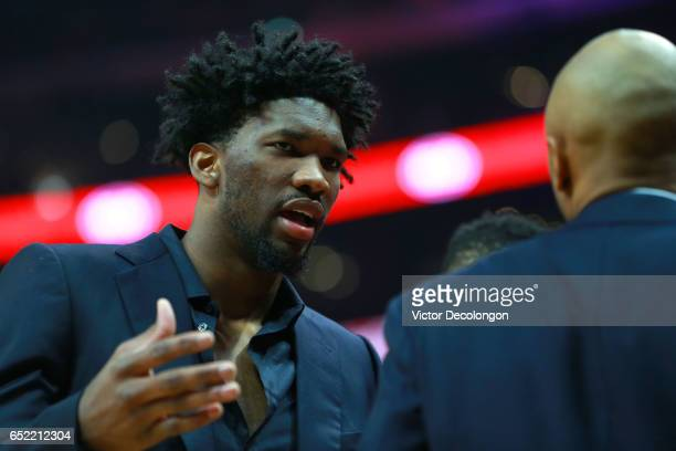 Injured Philadelphia 76ers player Joel Embiid left talks with a teammate near the bench area during a break in NBA game action between the...
