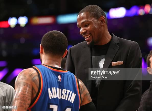 Injured player Kevin Durant of the Oklahoma City Thunder talks with DJ Augustin during the game against the Los Angeles Lakers at Staples Center on...