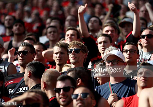 Injured player Stefan Kiessling of LEverkusen is seen in the stands with fans during the Bundesliga match between Bayer 04 Leverkusen and Hamburger...
