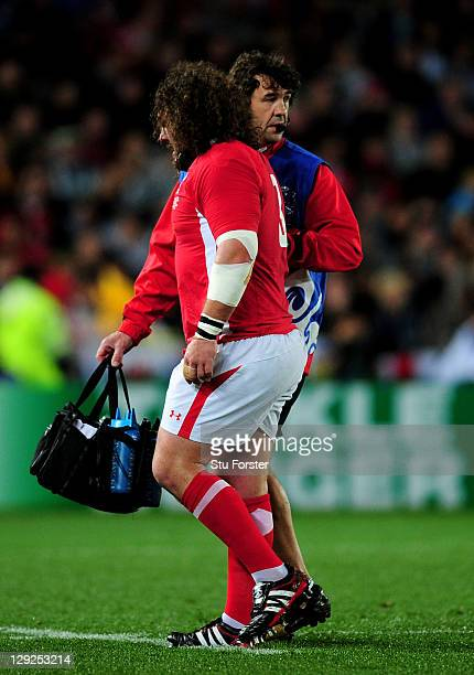 Injured prop Adam Jones of Wales is helped off the pitch by Physio Mark Davies during semi final one of the 2011 IRB Rugby World Cup between Wales...