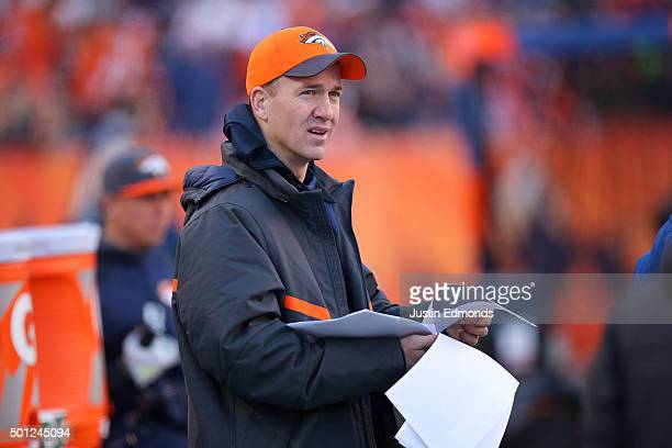 Injured quarterback Peyton Manning of the Denver Broncos looks over game notes on the sideline during a game against the Oakland Raiders at Sports...