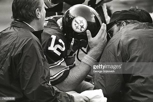 Injured quarterback Terry Bradshaw of the Pittsburgh Steelers is aided by team trainers during a game against the Dallas Cowboys at Three Rivers...